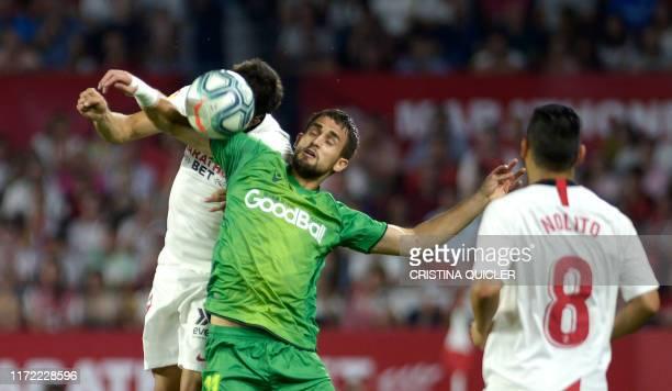 Real Sociedad's Belgian forward Adnan Januzaj jumps for the ball with Sevilla's Spanish defender Sergi Gomez during the Spanish league football match...