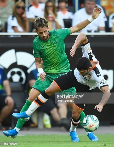 Real Sociedad's Belgian midfielder Adnan Januzaj challenges Valencia's Portuguese midfielder Goncalo Guedes during the Spanish League football match...