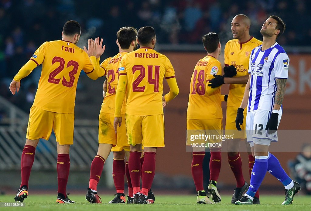 Real Sociedad's Brazilian forward Willian Jose (R) gestures as Sevilla players celebrate their 4th goal during the Spanish league football match Real Sociedad vs Sevilla FC at the Anoeta stadium in San Sebastian on January 7, 2017. / AFP / MIGUEL