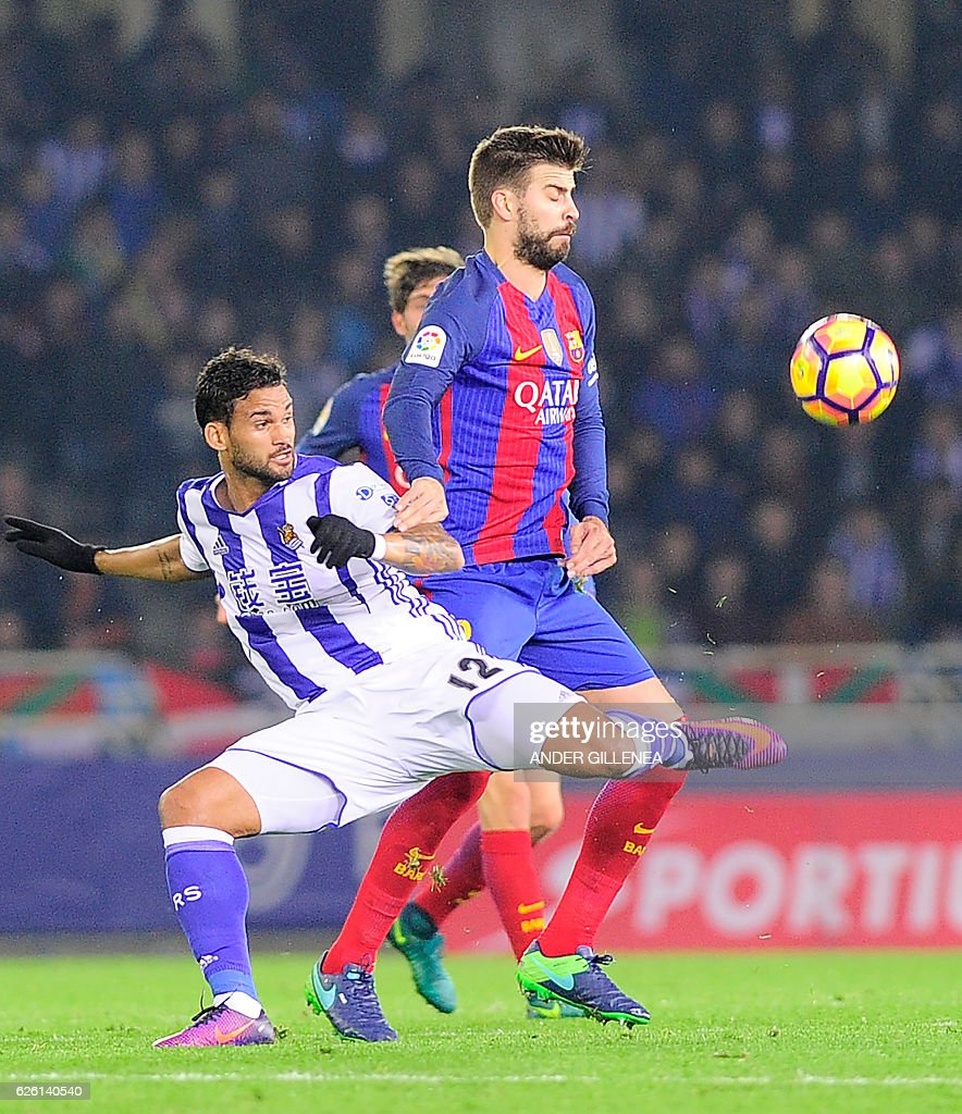 Real Sociedad's Brazilian forward Willian Jose (L) vies with Barcelona's defender Gerard Pique (R) during the Spanish league football match Real Sociedad vs FC Barcelona at the Anoeta stadium in San Sebastian, on November 27, 2016. / AFP / ANDER