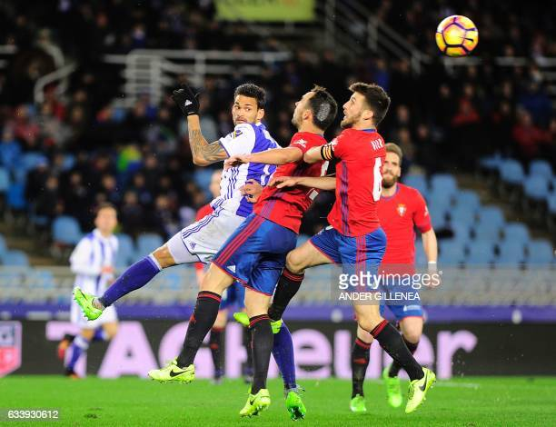 Real Sociedad's Brazilian forward Willian Jose vies with Osasuna's defender Unai Garcia and midfielder Oier Sanjurjo during the Spanish league...