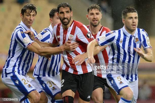 Real Sociedad's French defender Robin Le Normand and Real Sociedad's Spanish midfielder Igor Zubeldia challenge Athletic Bilbao's Spanish midfielder...