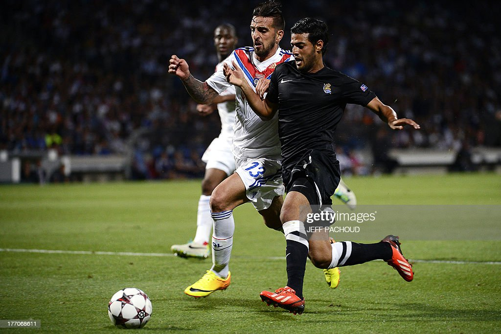 Real Sociedad's Mexican forward Carlos Vela (R) vies with Lyon's Portuguese defender Miguel Lopes (L) during the first leg of the UEFA Champions League's playoffs football match Olympique Lyonnais vs Real Sociedad on August 20, 2013 at the Gerland stadium in Lyon, eastern France.