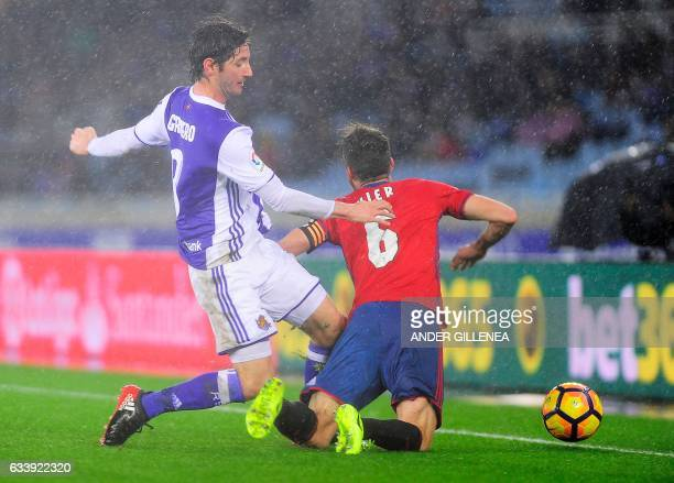 Real Sociedad's midfielder Esteban Granero vies with Osasuna's midfielder Oier Sanjurjo during the Spanish league football match Real Sociedad vs CA...