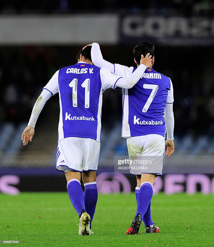 Real Sociedad's midfielder Juanmi (R) is congratulated by teammate Mexican forward Carlos Vela (L) after scoring his team's third goal during the Spanish league football match Real Sociedad vs Valencia CF at the Anoeta stadium in San Sebastian on December 10, 2016. / AFP / ANDER