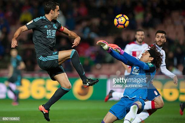 Real Sociedad's midfielder Xabi Prieto vies with Granada's Mexican goalkeeper Guillermo Ochoa during the Spanish league football match Granada CF vs...