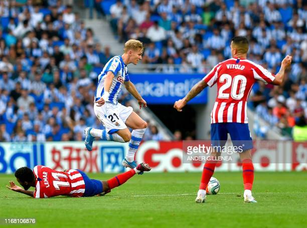 Real Sociedad's Norwegian midfielder Martin Odegaard jumps over Atletico Madrid's French midfielder Thomas Lemar during the Spanish league football...