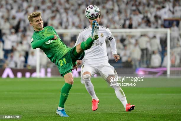 TOPSHOT Real Sociedad's Norwegian midfielder Martin Odegaard vies with Real Madrid's Spanish defender Sergio Ramos during the Spanish Copa del Rey...