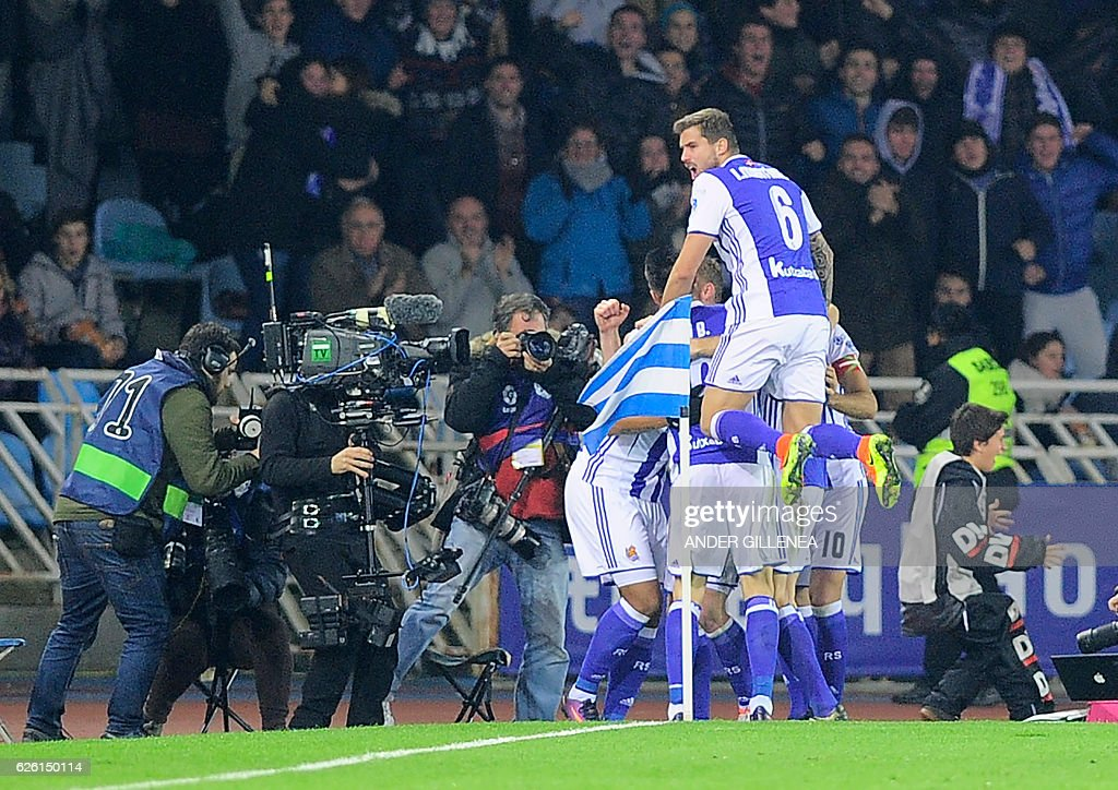 Real Sociedad's players celebrate after Brazilian forward Willian Jose scored a goal during the Spanish league football match Real Sociedad vs FC Barcelona at the Anoeta stadium in San Sebastian, on November 27, 2016. / AFP / ANDER