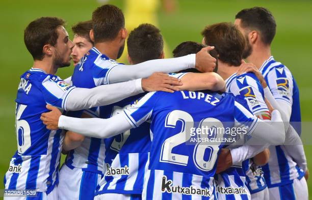 Real Sociedad's players celebrate teammate Spanish forward Mikel Oyarzabal's goal during the Spanish League football match between Real Sociedad and...
