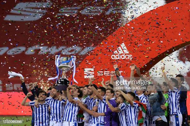 Real Sociedad's players celebrate with the trophy after winning the 2020 Spanish Copa del Rey final football match between Athletic Bilbao and Real...