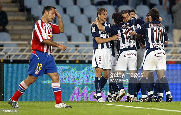 Real Sociedad's Serbian Darko Kovacevic celebrates his goal with his teammates as Atletico Madrid's Sergi Barjuan passes by 02 October 2004 during a...