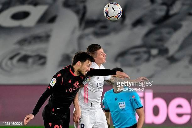 Real Sociedad's Spanish midfielder David Silva heads the ball with Real Madrid's German midfielder Toni Kroos during the Spanish league football...