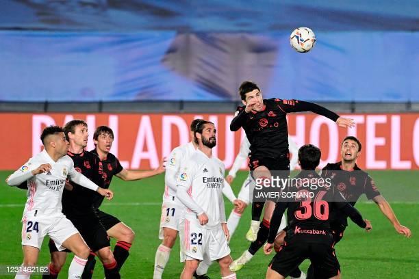 Real Sociedad's Spanish midfielder Igor Zubeldia jumps to head the ball next to Real Madrid's Spanish midfielder Isco during the Spanish league...