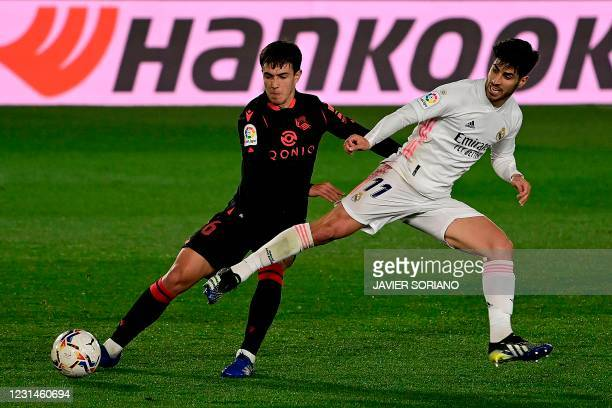 Real Sociedad's Spanish midfielder Martin Zubimendi challenges Real Madrid's Spanish midfielder Marco Asensio during the Spanish league football...