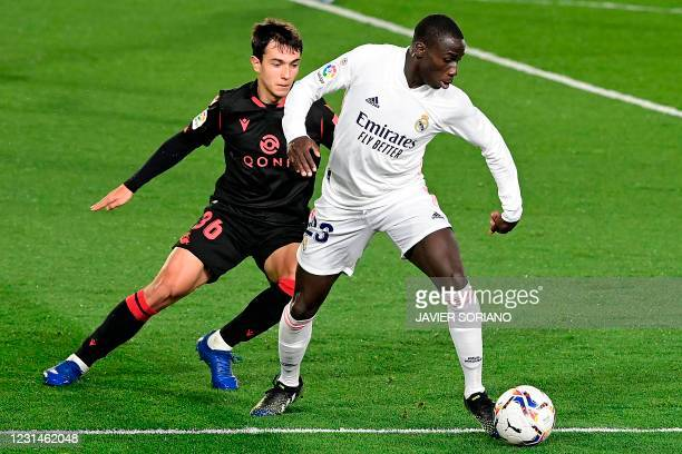 Real Sociedad's Spanish midfielder Martin Zubimendi challenges Real Madrid's French defender Ferland Mendy during the Spanish league football match...