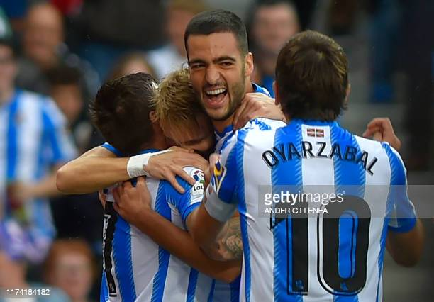 Real Sociedad's Spanish midfielder Mikel Merino celebrates his goal with teammates during the Spanish league football match between Real Sociedad and...