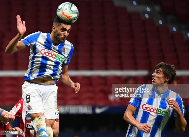 Real Sociedad's Spanish midfielder Mikel Merino heads the ball during the Spanish league football match between Club Atletico de Madrid and Real...