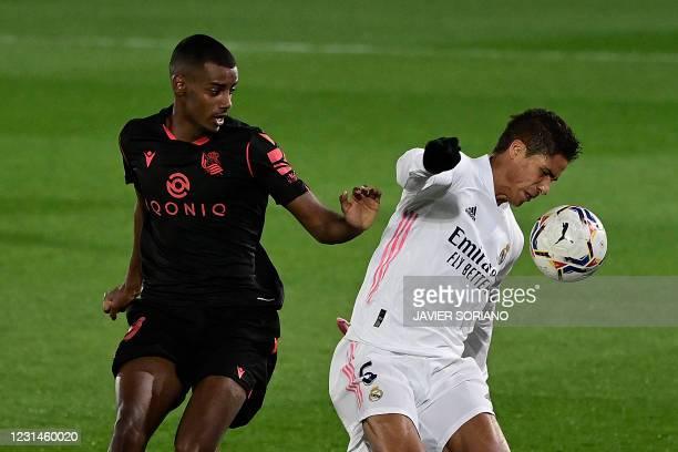 Real Sociedad's Swedish forward Alexander Isak challenges Real Madrid's French defender Raphael Varane during the Spanish league football match...