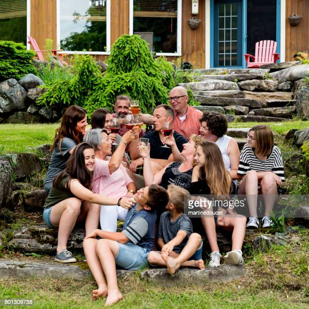 Echte drei-Generationen-Familie Toasten im Freien im Sommer.