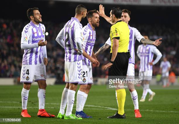 Real Valladolid CF players confront referee Juan Martinez Munuera after he awards Barcelona a penalty during the La Liga match between FC Barcelona...