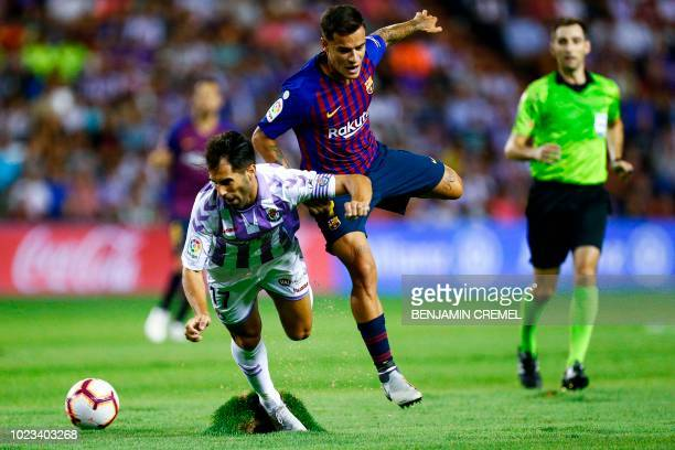 Real Valladolid's Spanish defender Javi Moyano falls beside Barcelona's Brazilian midfielder Philippe Coutinho during the Spanish league football...