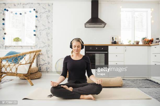 real woman at home in kitchen doing yoga and meditation - buddhism stock pictures, royalty-free photos & images