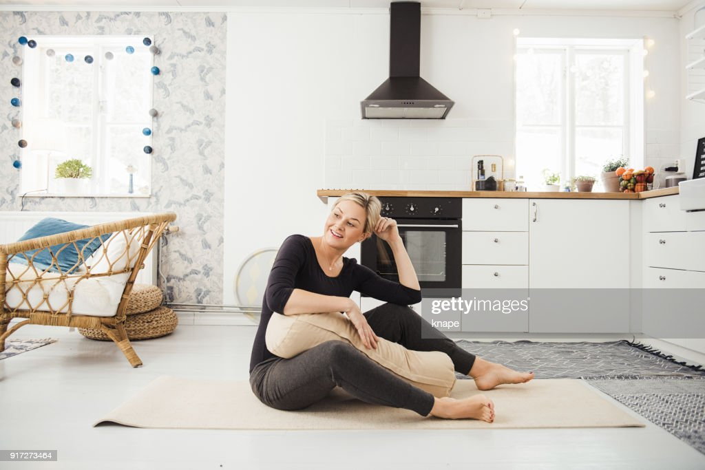 Real woman at home in kitchen doing yoga and meditation : Stock Photo