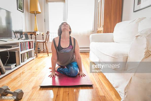 real woman doing yoga exercise in home living room - curvy women stock pictures, royalty-free photos & images