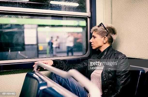 Real femme assise au métro et à la recherche dans la fenêtre