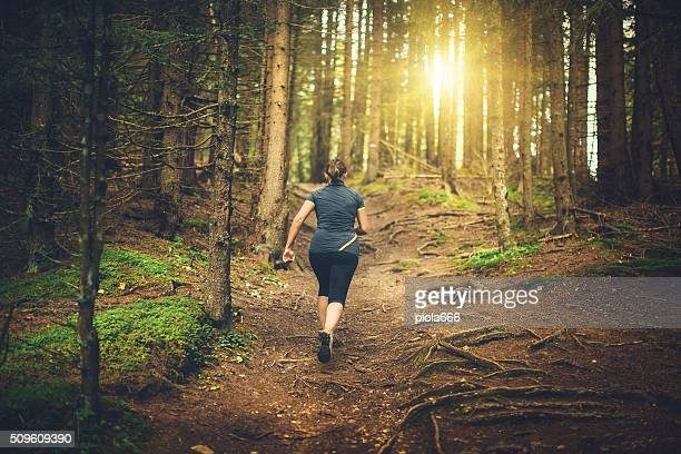 Real woman trail running in the forest