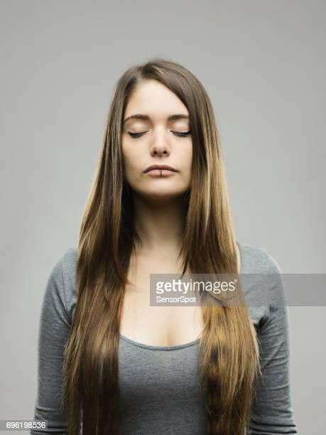 Echte jonge vrouw studio portret met gesloten ogen