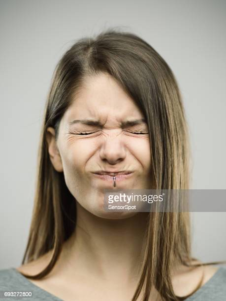 real young woman with pain expression - pain stock pictures, royalty-free photos & images