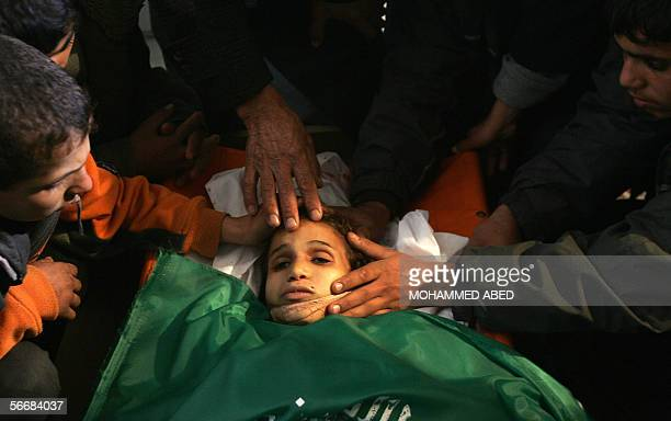 Realatives of a nineyearold Palestinian girl shot dead by Israeli troops mourn over her body covered by a Islamic Militant Hamas flag during her...