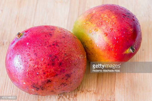Realistic approach to food beautiful imperfect mangoes with water droplets over wooden surface or cutting board
