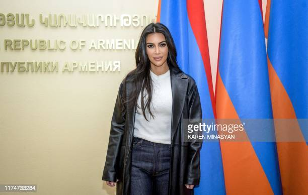 Reality television star Kim Kardashian poses by Armenian flags at the Armenian Government building during her visit in Yerevan on October 9, 2019. -...