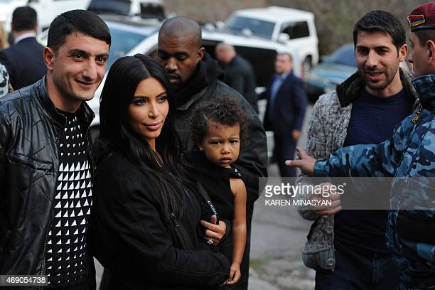 US reality TV star Kim Kardashian with her rapper husband Kanye West and their daughter North on April 9 2015 pose with local residents near the...