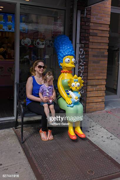 Reallife mother and child with Marge and Maggie Simpson characters in Manhattan New York City Sitting next to the fictional mother the reallife mom...