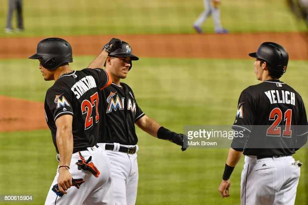 T Realmuto celebrates a 3 run homer with Giancarlo Stanton and Christian Yelich of the Miami Marlins during the game between the Miami Marlins and...