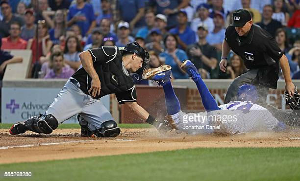 T Realmuto of the Miami Marlins drops the ball as he tries to tag Dexter Fowler of the Chicago Cubs at the plate in the 3rd inning at Wrigley Field...