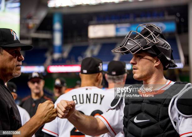 T Realmuto of the Miami Marlins fistbumps pitching coach Juan Nieves after the game against the Atlanta Braves at Marlins Park on September 28 2017...