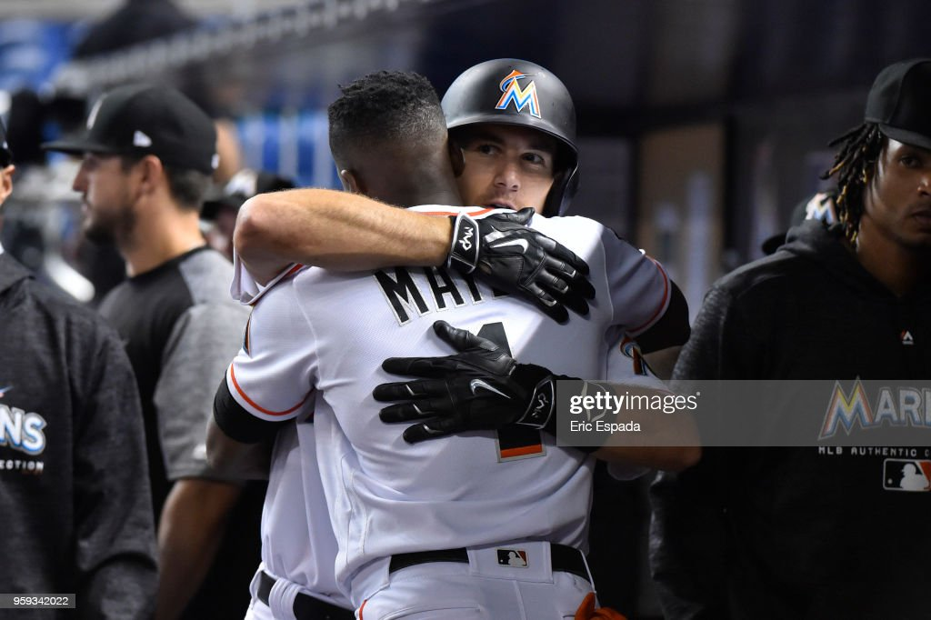 J.T. Realmuto #11 of the Miami Marlins hugs Cameron Maybin after hitting a home run in the sixth inning against the Los Angeles Dodgers at Marlins Park on May 16, 2018 in Miami, Florida.