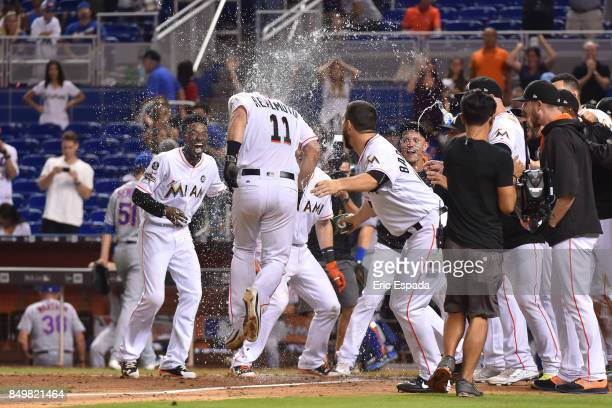T Realmuto of the Miami Marlins is congratulated by teammates after hitting a walk off home run in the tenth inning against the New York Mets at...