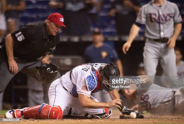 T Realmuto of the Miami Marlins misses the tag at homeplate on Daniel Robertson of the Tampa Bay Rays in the ninth inning against the Tampa Bay Rays...