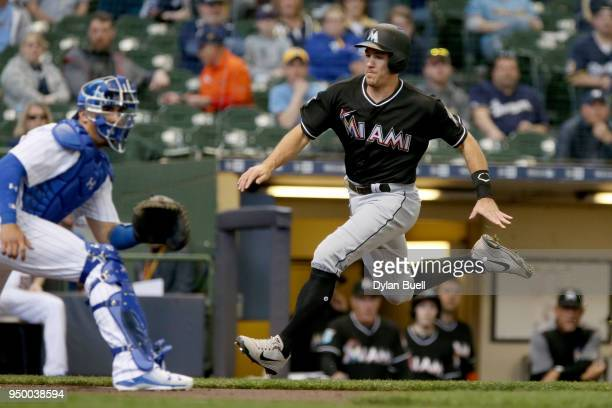 T Realmuto of the Miami Marlins runs to home plate to score a run past Jacob Nottingham of the Milwaukee Brewers in the first inning at Miller Park...