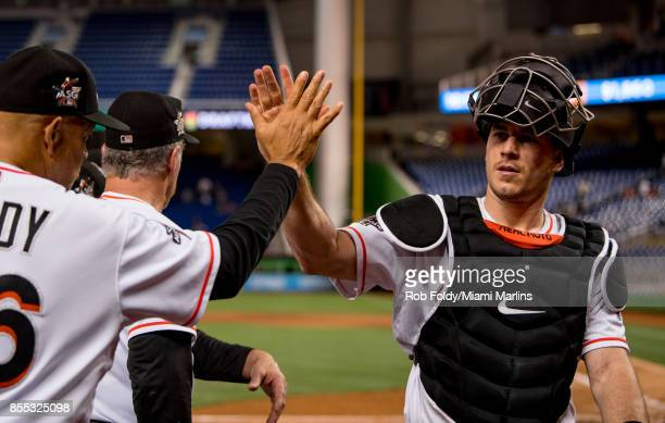 T Realmuto of the Miami Marlins slaps hands with outfield/baserunning coach Lorenzo Bundy after the game against the Atlanta Braves at Marlins Park...