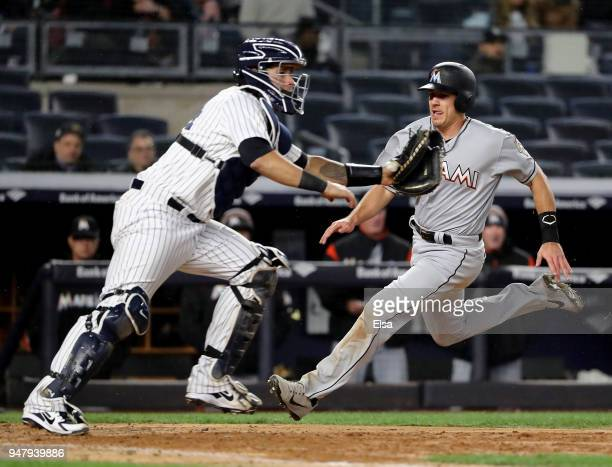 T Realmuto of the Miami Marlins slides home safely as Gary Sanchez of the New York Yankees defends in the eighth inning at Yankee Stadium on April 17...