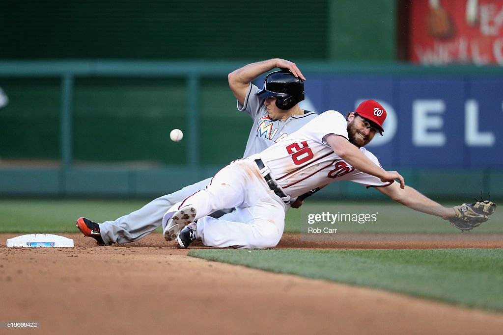J.T. Realmuto #11 of the Miami Marlins steals second base as Daniel Murphy #20 of the Washington Nationals misses the ball in the third inning at Nationals Park on April 7, 2016 in Washington, DC.