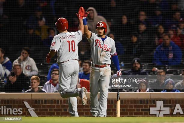 T Realmuto of the Philadelphia Phillies is congratulated by Cesar Hernandez following a home run against the Chicago Cubs during the 10th inning at...