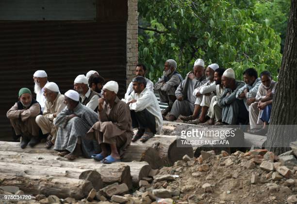 Realtives and neighbours of a slain editorinchief of the Srinagarbased newspaper Rising Kashmir Shujaat Bukhari mourn during the funeral procession...